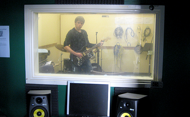 a student recording music in a studio
